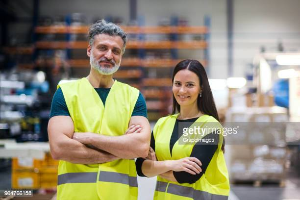 An industrial man and woman engineers in a factory, arms crossed.