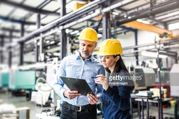 An industrial man and woman engineers in a factory checking documents.