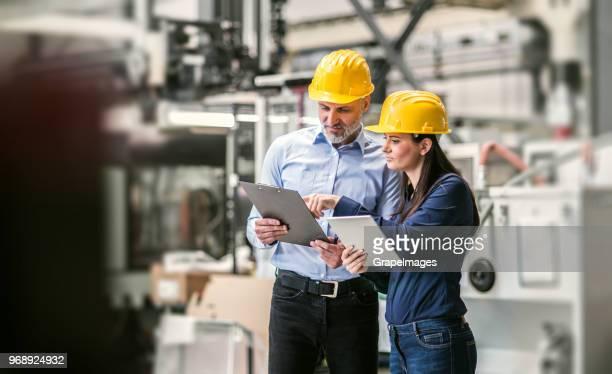 um homem industrial e engenheiros de mulher com o tablet em uma fábrica de verificação de documentos. - capacete equipamento - fotografias e filmes do acervo