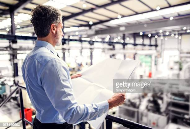 An industrial man engineer in a factory looking at blueprints. Copy space.