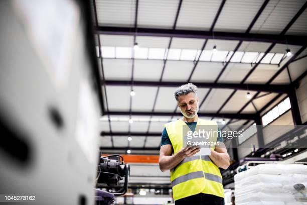 industrielle mann ingenieur arbeitet in einer fabrik, sich notizen macht. - westen stock-fotos und bilder