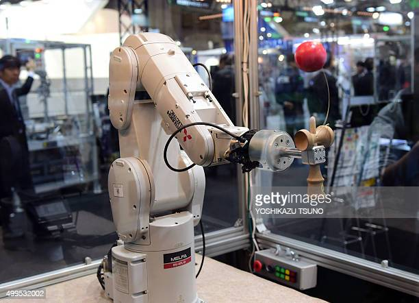 An industrial robot made by Mitsubishi Electric plays a traditional Japanese game called kendama similar to a cupandball game during a demonstration...
