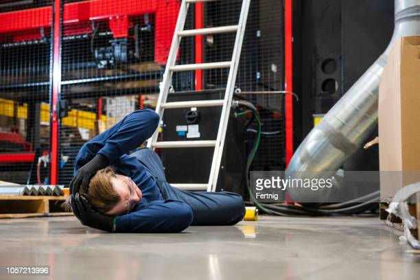 an industrial, safety, manufacturing topic.  a worker having fallen off a ladder in a factory. - head injury stock photos and pictures
