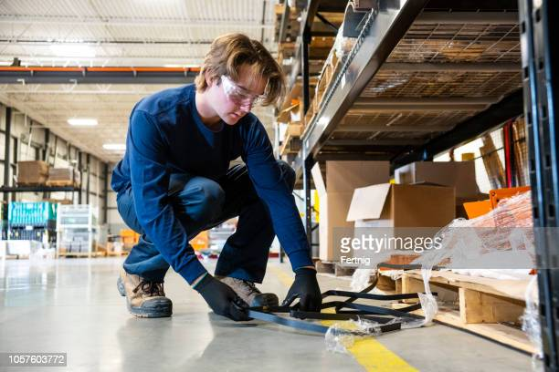 an industrial safety topic.  a worker picks-up trash from the floor in a manufacturing plant. - tripping falling stock pictures, royalty-free photos & images
