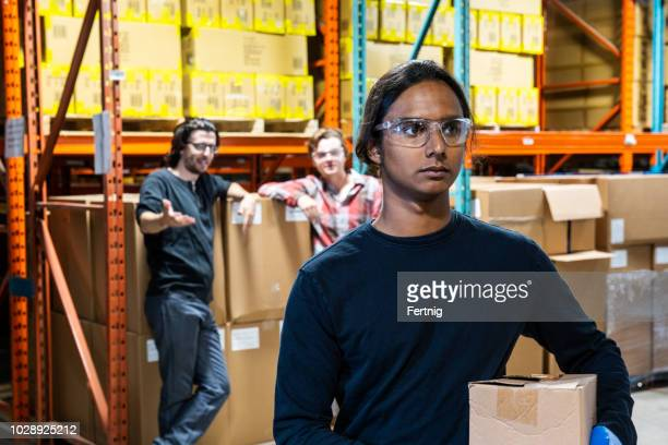 an industrial warehouse worker being the target of bullying - prejudice stock pictures, royalty-free photos & images