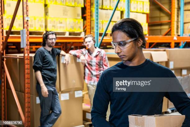 an industrial warehouse worker being the target of bullying - gossip stock pictures, royalty-free photos & images