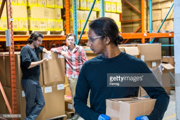 an industrial warehouse worker being the target of bullying - preconceito racial imagens e fotografias de stock