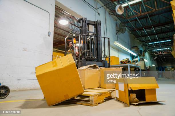 an industrial warehouse workplace safety and asset protection topic.  a forklift driver crashes into and damages merchandise by driving carelessly. - damaged stock pictures, royalty-free photos & images