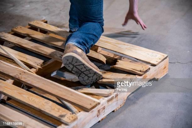 um armazém industrial, tópico de segurança no local de trabalho.  um close-up de uma pessoa que pisa em uma pálete quebrada. - bater - fotografias e filmes do acervo