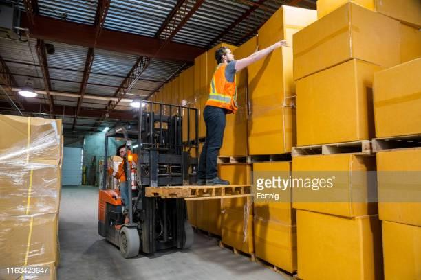 un tema de seguridad en el lugar de trabajo de almacén industrial. una situación peligrosa como trabajador es levantada por una carretilla elevadora para llegar a la mercancía de mayor ubicación. - alto posición descriptiva fotografías e imágenes de stock
