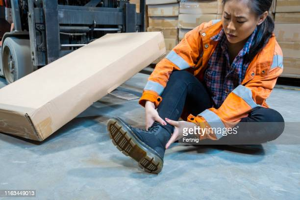 an industrial warehouse workplace safety topic.  a female employee injured by tripping over forklift forks. - tripping falling stock pictures, royalty-free photos & images