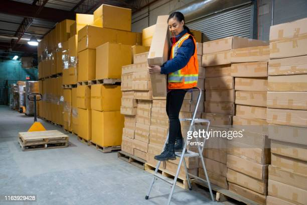 an industrial warehouse workplace safety topic. a female employee incorrectly steps down from a short step ladder to reach some higher placed merchandise. - step ladder stock photos and pictures