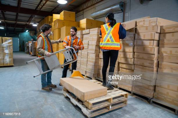 an industrial warehouse workplace safety topic.  a female employee uses a pallet jack loaded with pallets as a step to reach higher placed boxes. - step ladder stock pictures, royalty-free photos & images