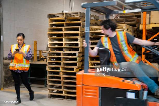 an industrial warehouse workplace safety topic. a female worker distracted by her mobile cell phone as a forklift approaches. - danger stock pictures, royalty-free photos & images