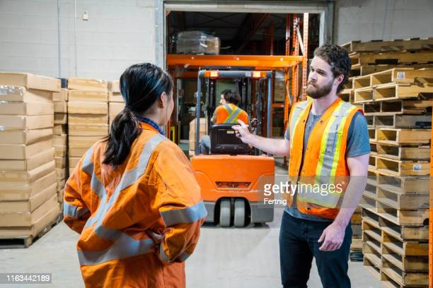 an industrial warehouse workplace safety topic. a manager discusses an issue about a forklift driver. - conflict stock pictures, royalty-free photos & images