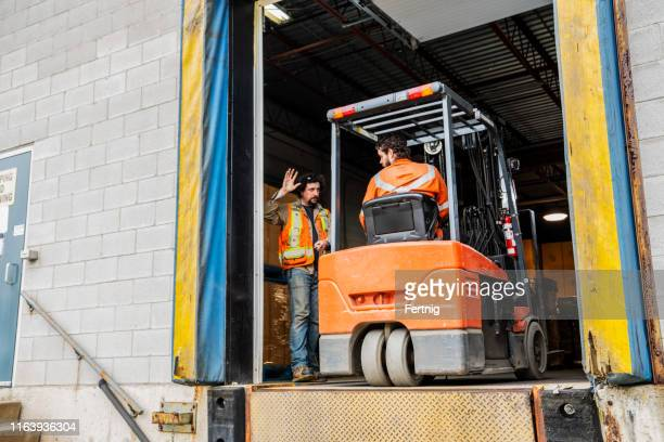 an industrial warehouse workplace safety topic.  a manager or supervisor stops a forklift driver from backing up over a loading dock. - loading dock stock pictures, royalty-free photos & images