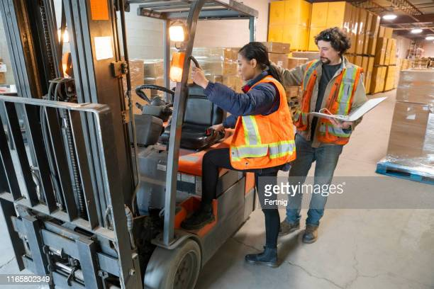 an industrial warehouse workplace safety topic.  a safety supervisor or manager training a new employee on forklift safety. - occupational safety and health stock pictures, royalty-free photos & images