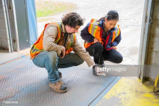 an industrial warehouse workplace safety topic.  a supervisor or manager explains the danger involved with lifting and dropping loading dock plates. - loading dock stock pictures, royalty-free photos & images