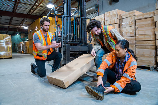 An industrial warehouse workplace safety topic. A worker injured falling or being struck by a forklift. 1163443516