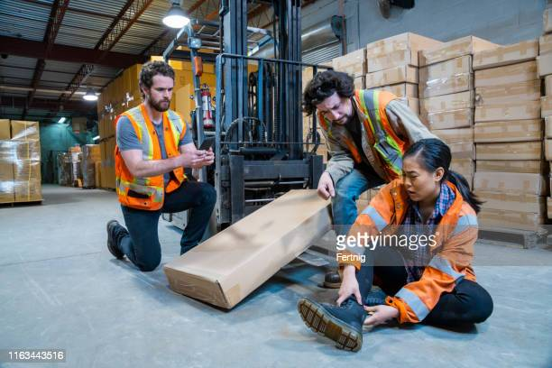an industrial warehouse workplace safety topic. a worker injured falling or being struck by a forklift. - crash stock pictures, royalty-free photos & images