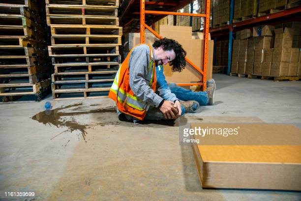 An industrial, warehouse, workplace safety topic.  An employee falls injuring himself by slipping on a plastic water bottle.