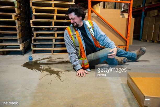 産業、倉庫、職場の安全に関するトピック。 従業員がペットボトルを滑ってけがをしました。 - 状態 ストックフォトと画像