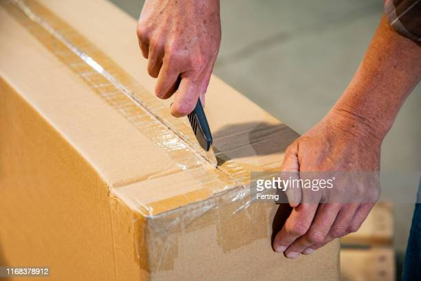 an industrial workplace warehouse safety topic. a female cutting a box using a utility knife. - utility knife stock pictures, royalty-free photos & images