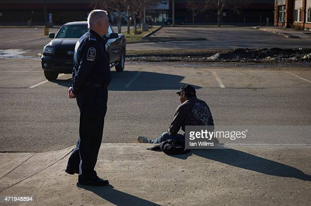An inebriated man sits in front of a liquor store in downtown Fort McMurray April 26th 2015 Fort McMurray is currently coping with an economic...