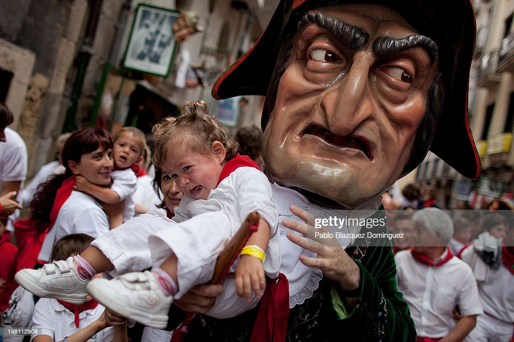 An infant being held by bigheaded Caravinagre 'Vinegar face' cries during the Kiliki parade on the fourth day of the San Fermin running-of-the-bulls on July 10, 2012 in Pamplona, Spain. Pamplona's famous Fiesta de San Fermin, which involves the running of the bulls through the historic heart of Pamplona for eight days starting July 7th, was made famous by the 1926 novel of U.S. writer Ernest Hemmingway called 'The Sun Also Rises.'