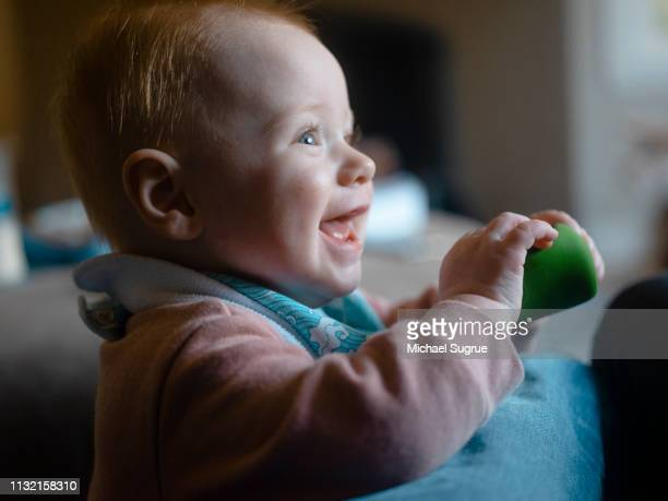 An infant child laughs while playing at home.