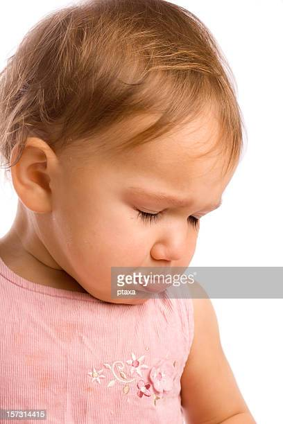 An infant girl pouting in a pink outfit