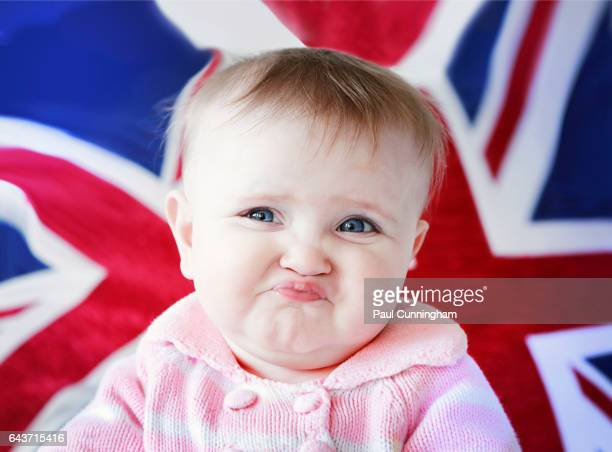 An infant having fun making a face and blowing raspberries