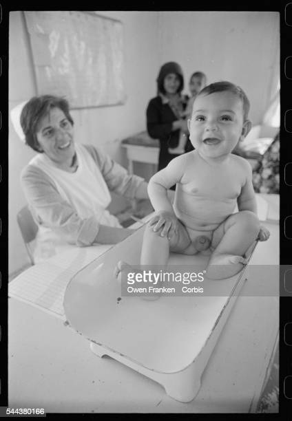 An infant Palestinian refugee is attended to in a clinic sponsored by the United Nations Relief and Works Agency
