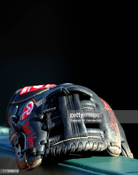 An infielders glove belonging to a Cleveland Indian sits on the dugout rail during batting practice before a MLB baseball game against the San...