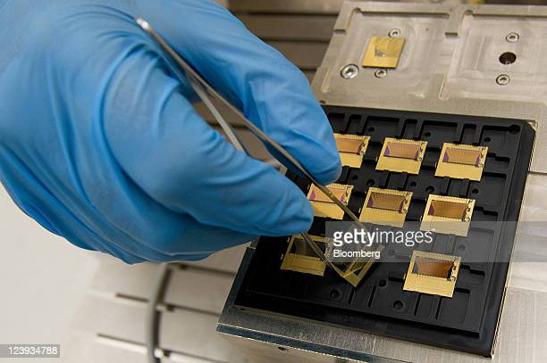 An Infinera Corp employee puts a completed largescale photonic integrated circuit into a tray readied for insertion into an automated packaging...