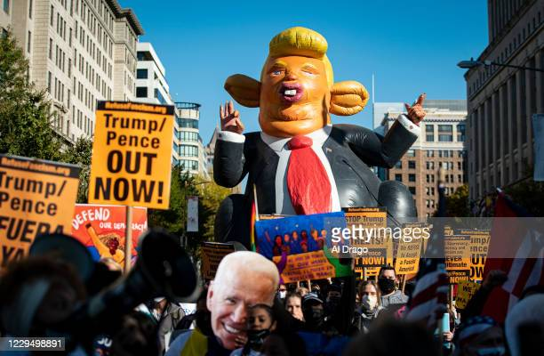An inflatable balloon of U.S. President Donald Trump is carried as people march to Black Lives Matter Plaza during a demonstration organized by...