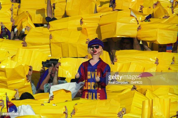 An inflatable Barcelona fans smokes on a cigar surrounded by yellow cards as the fans soak up the atmosphere.