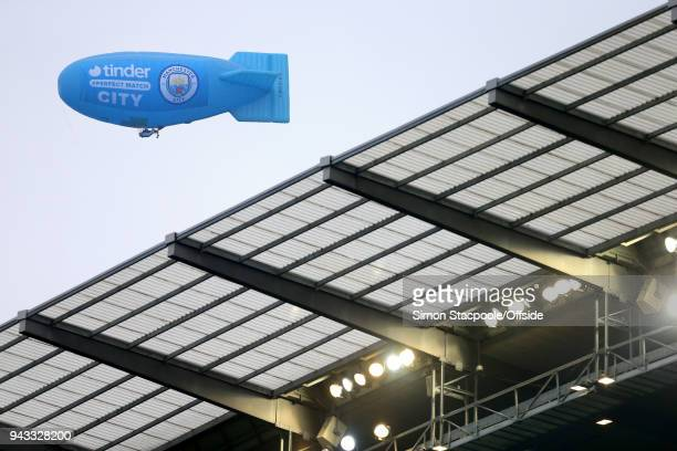 An inflatable blimp advertising Man City's newest sponsor the dating app Tinder hovers above the stands during the Premier League match between...