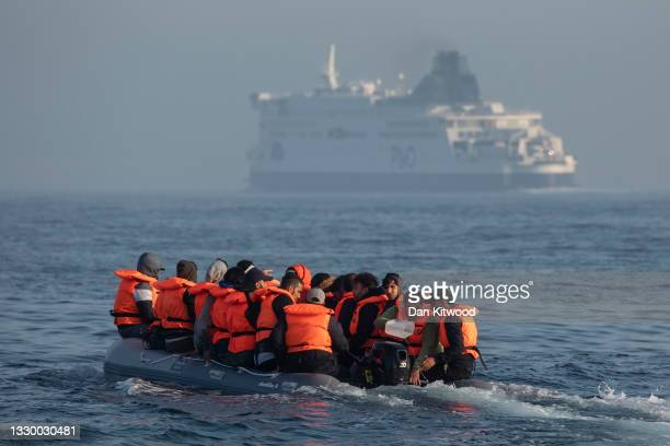 An inflatable craft carrying migrant men, women and children crosses the shipping lane in the English Channel on July 22, 2021 off the coast of...