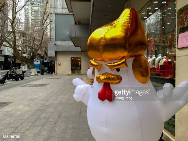 An inflatable rooster figure with a Donald Trump hairstyle and hand gestures stands outside a gold shop to attract customers