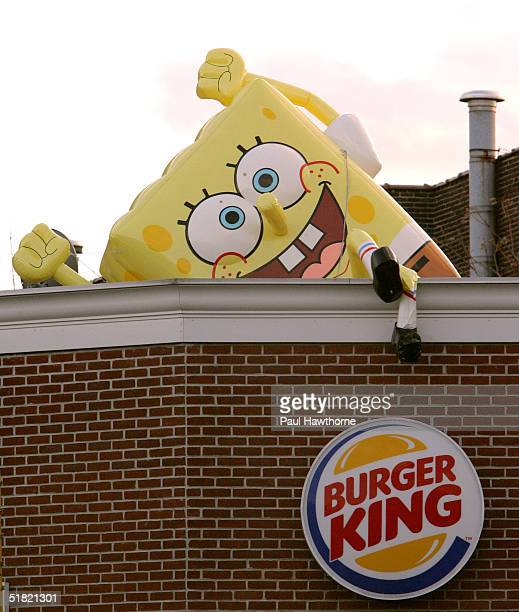 An inflatable SpongeBob Squarepants sits atop a Burger King December 3 2004 in Jersey City New Jersey More than 100 inflatable SpongeBobs have been...