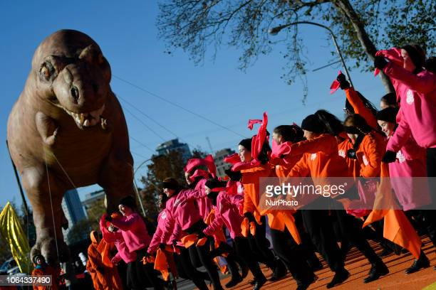 An inflatable Trex hoovers over dancers while standing by for the live broadcast of the 99th 6ABC/Dunkin' Donuts Annual Thanksgiving Day parade at...