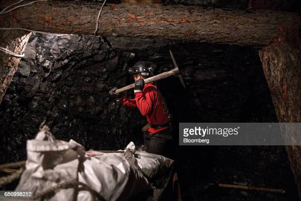 An informal coal miner uses a pickaxe to hack at a coal deposit underground at a coal mine shaft in Nailakh Ulaanbaatar Mongolia on Thursday March 16...