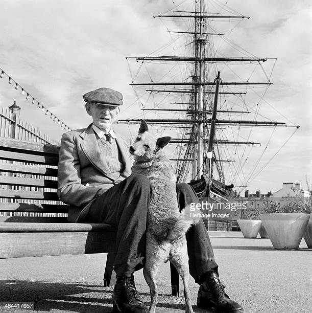 An informal portrait of a man and his dog seated in front of the Cutty Sark at Greenwich c1954c1980