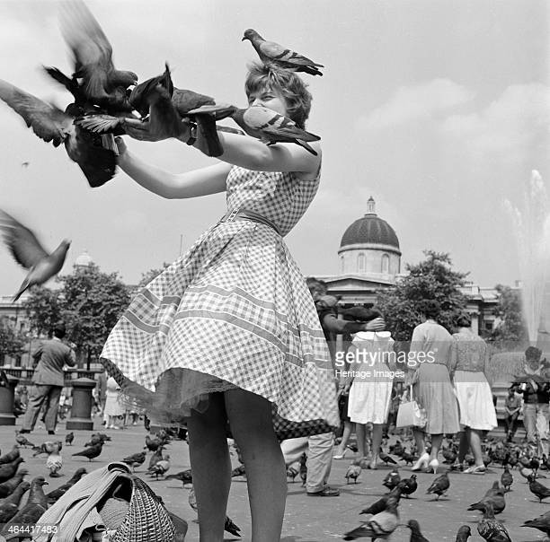 An informal portrait of a young woman in a gingham dress feeding the pigeons in Trafalgar Square Westminster London c1946c1959