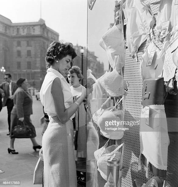 An informal portrait of a young woman looking in the window of a lingerie shop in Piccadilly Circus Mayfair Westminster London c1946c1959