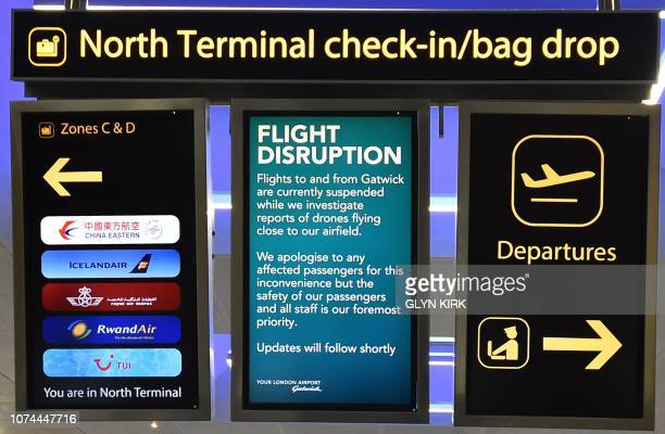 An information board announces flight disruption at London Gatwick Airport south of London on December 20 2018 after all flights were grounded due to...