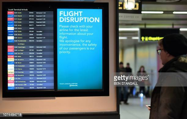 An information board displays flight information follwing disruption in the South Terminal building at London Gatwick Airport south of London on...