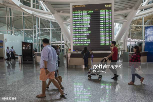 An information screen displays cancelled flights at Ngurah Rai International Airport near Denpasar Bali Indonesia on Tuesday Nov 28 2017 The airport...