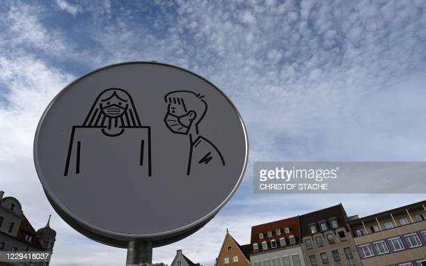 An information sign requesting to wear face masks is seen in the city of Augsburg, southern Germany, on November 2, 2020 amid the ongoing novel...